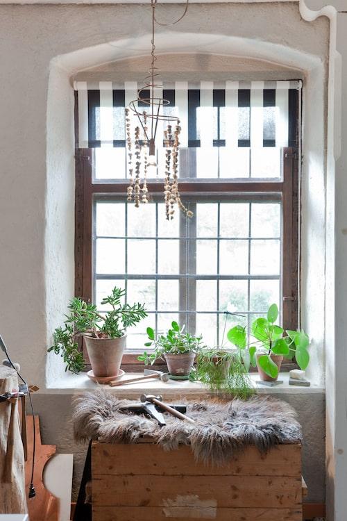 I fönstret i ateljén hänger en lampa som Marie gjort av snurrad koppartråd och torkade maskrosblommor som trätts på ståltråd.