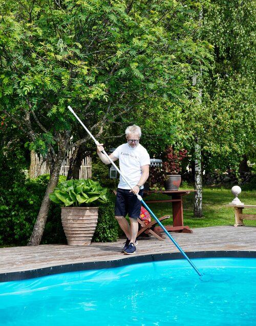 Göran går sin dagliga tur med håven och fiskar upp skräp ur poolen.