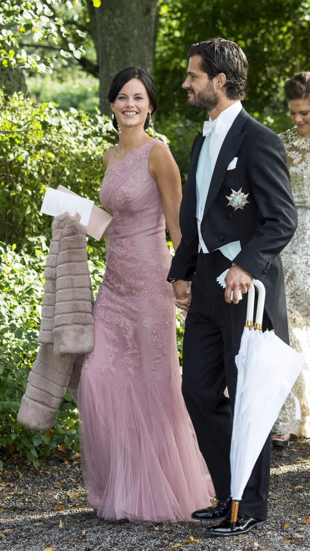 Prinsessan Sofia i rosa långklänning tillsammans med prins Carl Philip på ett bröllop.