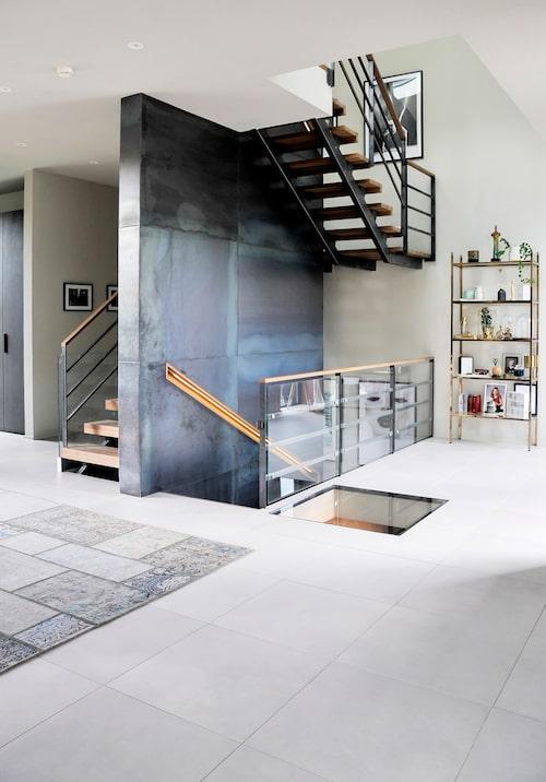 Trappans mittparti är klätt med industriplåt. Trappsteg i massiv ädelträtilja av ek, Almedals golv. Genom glasrutan i golvet kan man titta ner till vinkällaren.