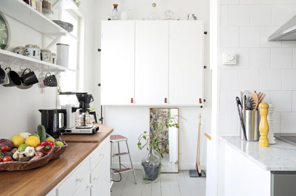 Arbetsdelen i köket är ett 80-talskök med ommålade luckor. För att få en känsla av rymd har överskåpen ersatts av hyllor från Ikea.