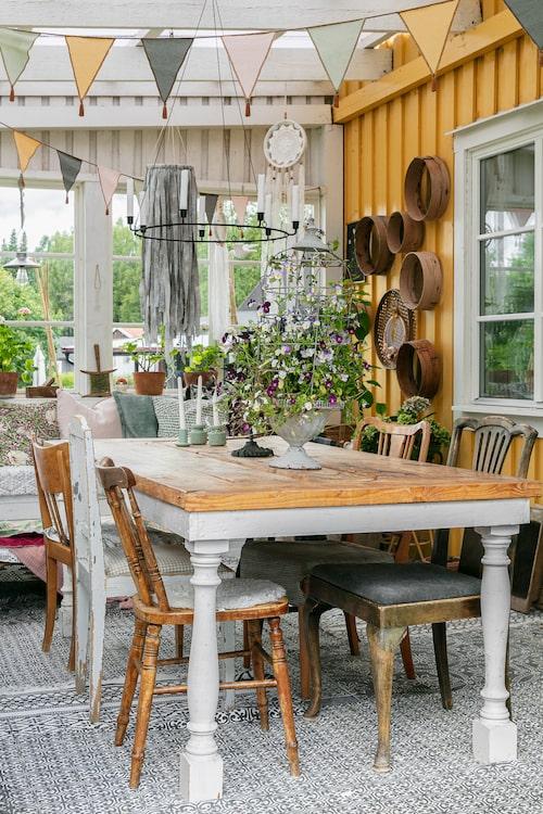 På verandan kan familjen samlas kring det rustika bordet som är tillverkat av en möbelsnickare i Gamla Stan i Stockholm. En soffa med många kuddar gör det extra ombonat. På verandan får även Lindas många sticklingar och dahliaknölar plats.