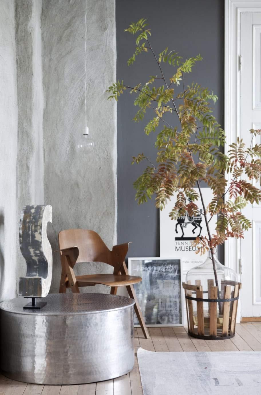 Den höga murstocken har putsats med betong. Retrostolen i teak är en favorit och kommer från NK-möbler. Tavlan med vit bakgrund är ett minne från tiden då skolhuset var ett tennfigursmuseum.