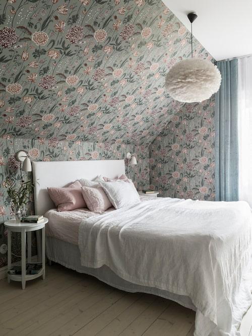 För att få plats med sänggavel under snedtaket tillverkade Lina en själv. Romantisk tapet, Aurélie, från Sandberg Wallpaper. Sängkappa, lakan och överkast i krusigt linne, taklampan med fjädrar är från Eos.