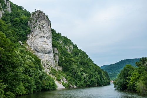 En gigantisk skulptur av kung Decebalus blickar ner över Donau.