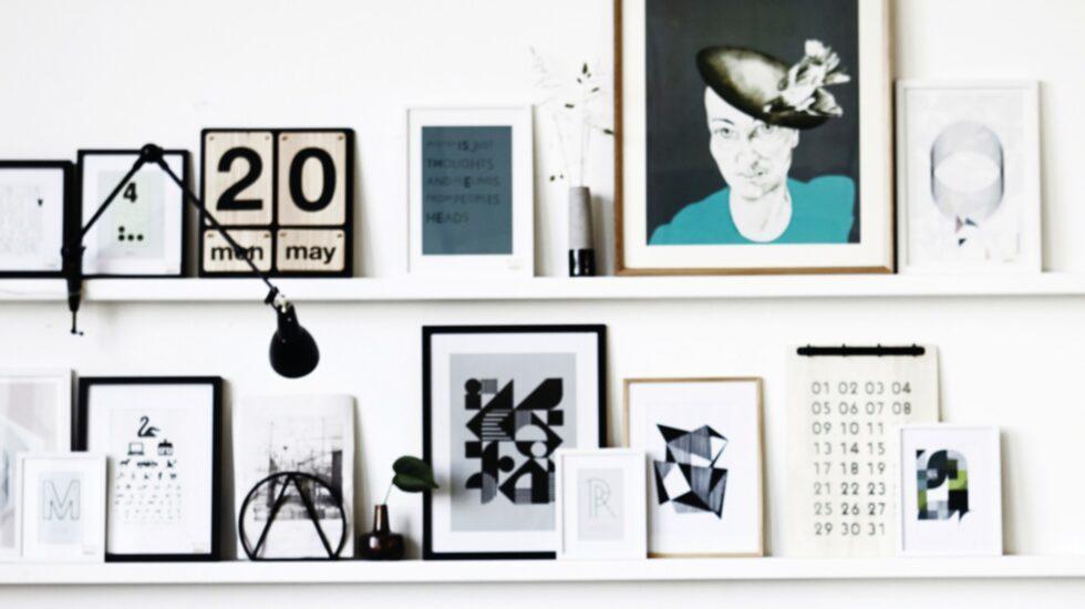 Sätt upp parallella tavellister på en vägg i vardagsrummet och blanda affischer, kort och prylar.