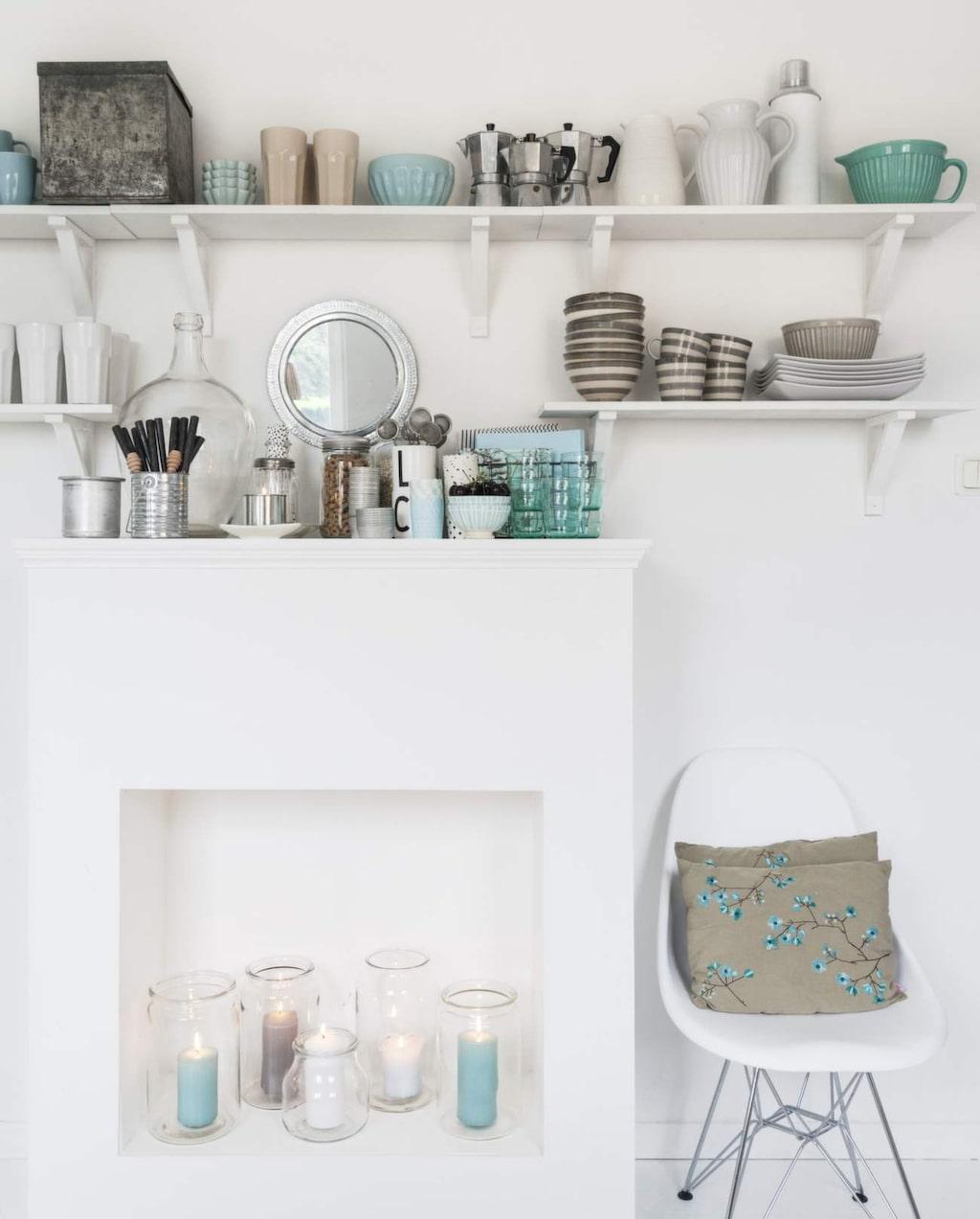 Spisen som är ett hemmabygge blir en bra möbel att ställa ingredienser och köksredskap på. På kvällarna lyser ljusen upp till ett vackert sken i det vita köket.