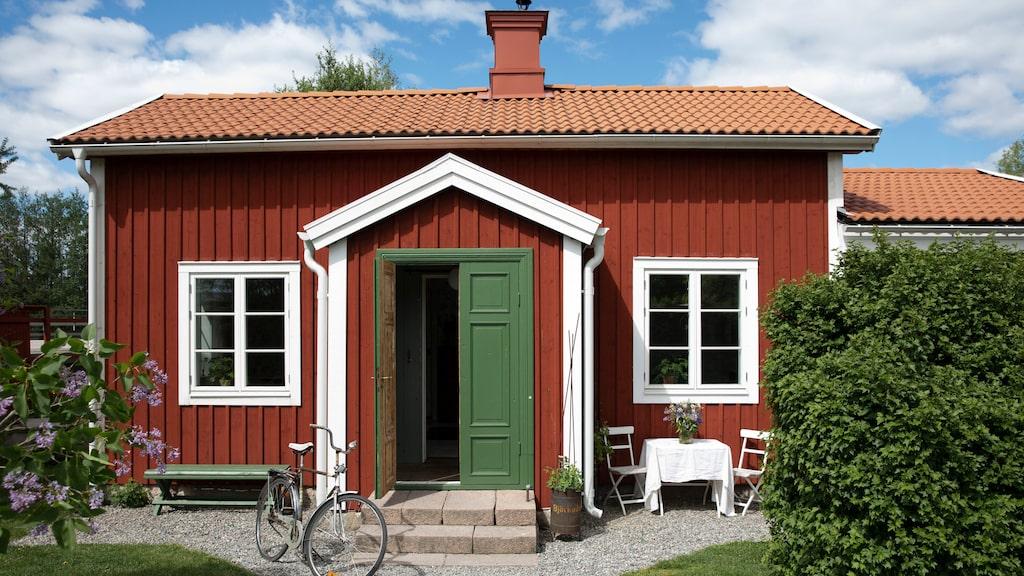Den slitna gamla banvaktstugan har blivit en riktig torpidyll i rött med vita knutar. Vita trädgårdsmöbler i metall, Ikea. Linneduk och vas är loppisfynd.