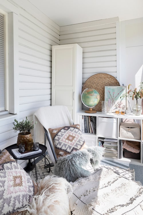 Den inglasade balkongen är lika välinredd och ombonad som resten av hemmet. Kuddar, H&M Home och Ikea. Sideboard, Ikea. Jordglob, gåva från farfar som har hängt med sedan Anna var barn. Flätad bricka, Affari of Sweden.