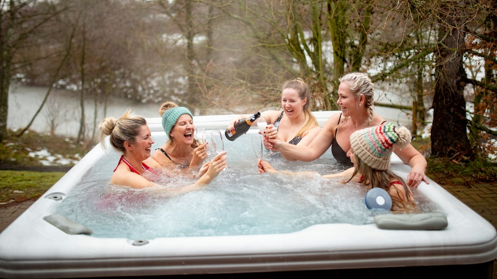 A young woman pours champagne for her friends in the hot tub whilst on a skiing holiday.