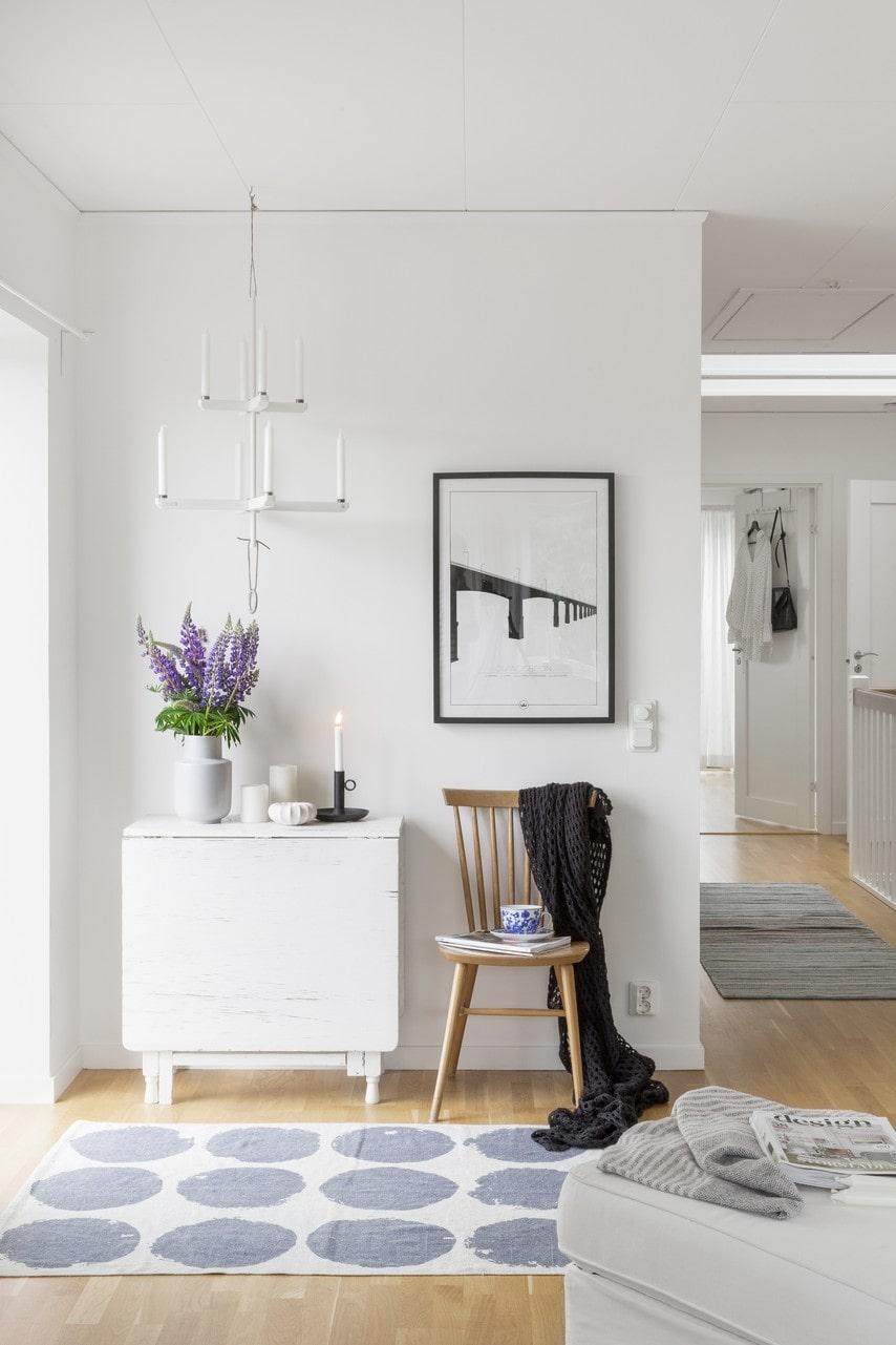 Nytt blandas med gammalt i hallen på övervåningen. Ljuskrona, Ernst. Slagbord, arvegods. Matta, Lagerhaus. Tavla, Sverigemotiv.