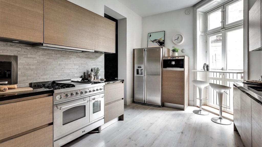 Det platsbyggda köket har gasspis, ugn, mikro, kyl/frys med ismaskin samt integrerad diskmaskin. Bra med förvaring och arbetsytor. Ljus stavmosaik över arbetsbänk i svart granit. Fransk balkong mot innergården.