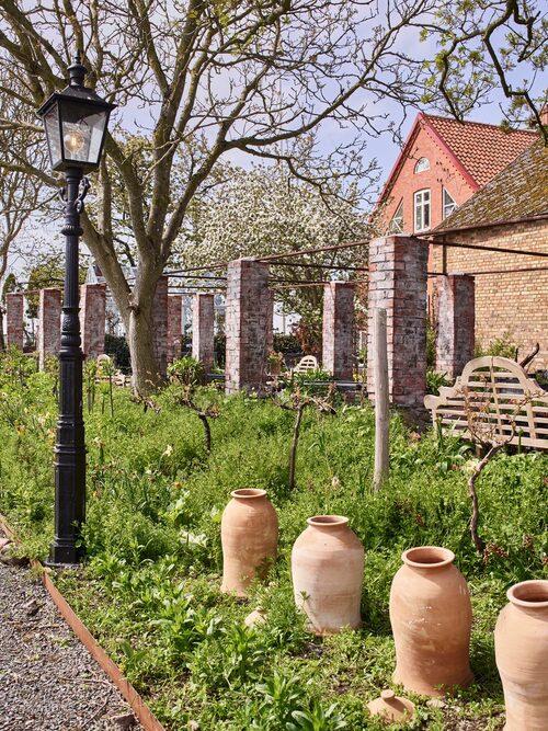 Trädgårdens pelargång av tegel har patinerats med filmjölk och puts.