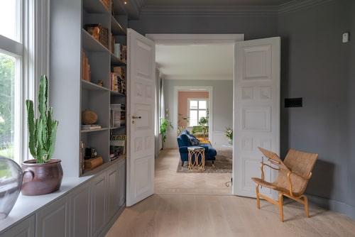 Paret älskar rummen som går i fil och lyxen i att kunna ha olika rum för olika tillfällen. Från biblioteket ser man genom stora salen bort till cocktailrummet. Fåtölj Eva, av Bruno Mathsson.