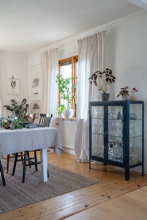 Vitrinskåpet är ett av få moderna inslag i matsalen. Vitrinskåp och matta, Ikea. Linneduk, H&M Home.
