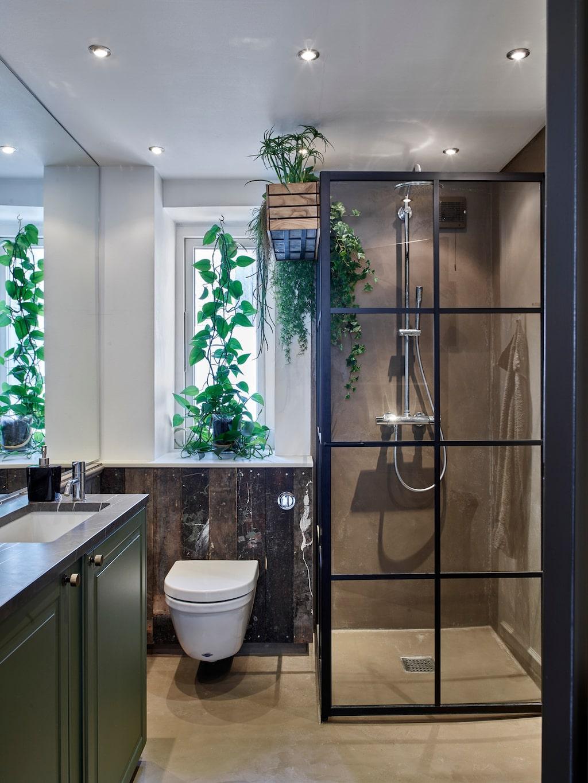 Panelen i badrummet är gjord av återvunna brädor. Duschkabin, Macro Design. På sidan av duschkabinen har Jeppe hängt en balkonglåda med växter.