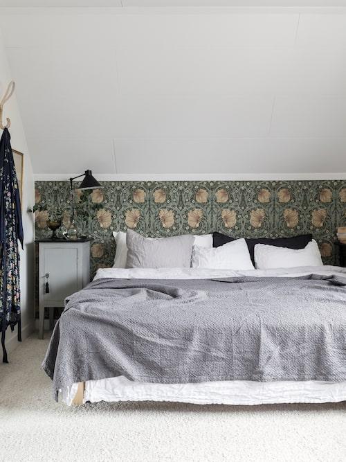 Camilla är förtjust i storblommiga tapeter i dova färger. Tapet, Pimpernel, William Morris. Sängbord, Auktionsverket. Sängkläder, H&M Home och Granit.