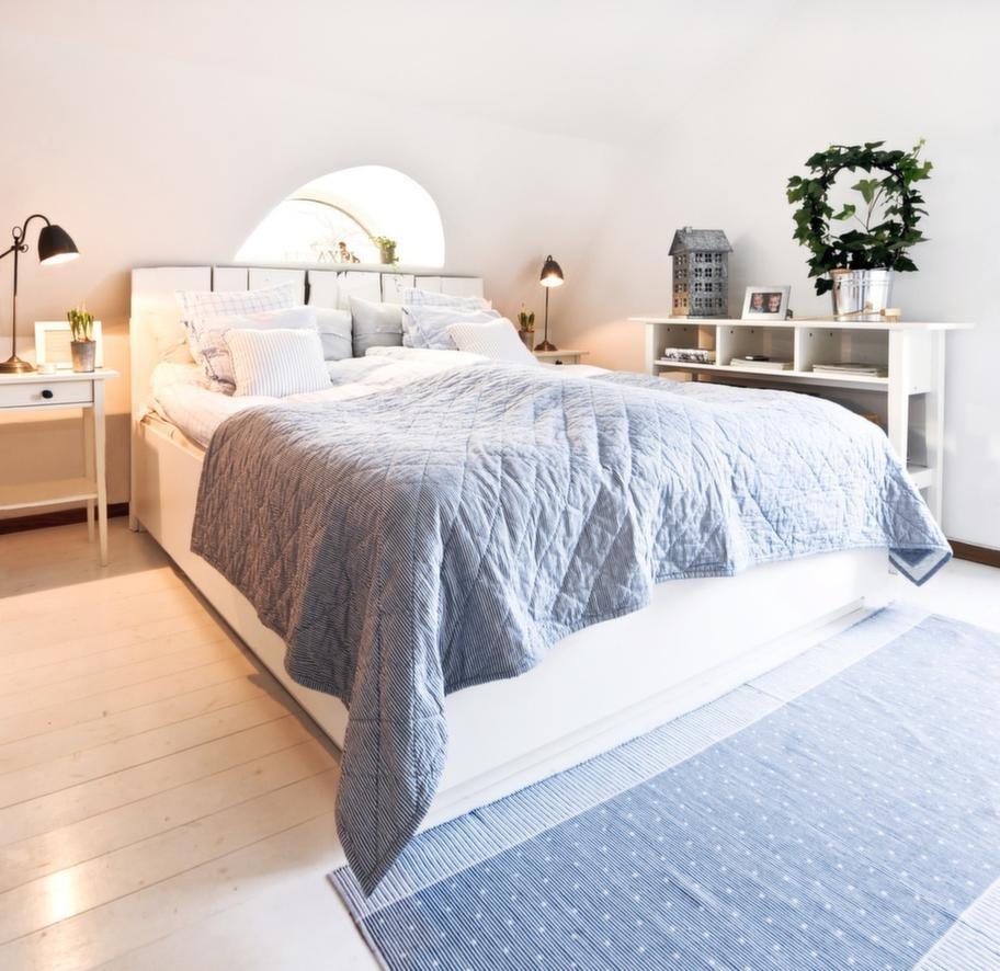 Svala färgerDet halvmåneformade fönstret i fint möte med sänggaveln, snickrad av plankor från säteriets lada. Ljusblå textilier från Nyblom Kollén. Ljushus i zink från Butik Stora Holm.