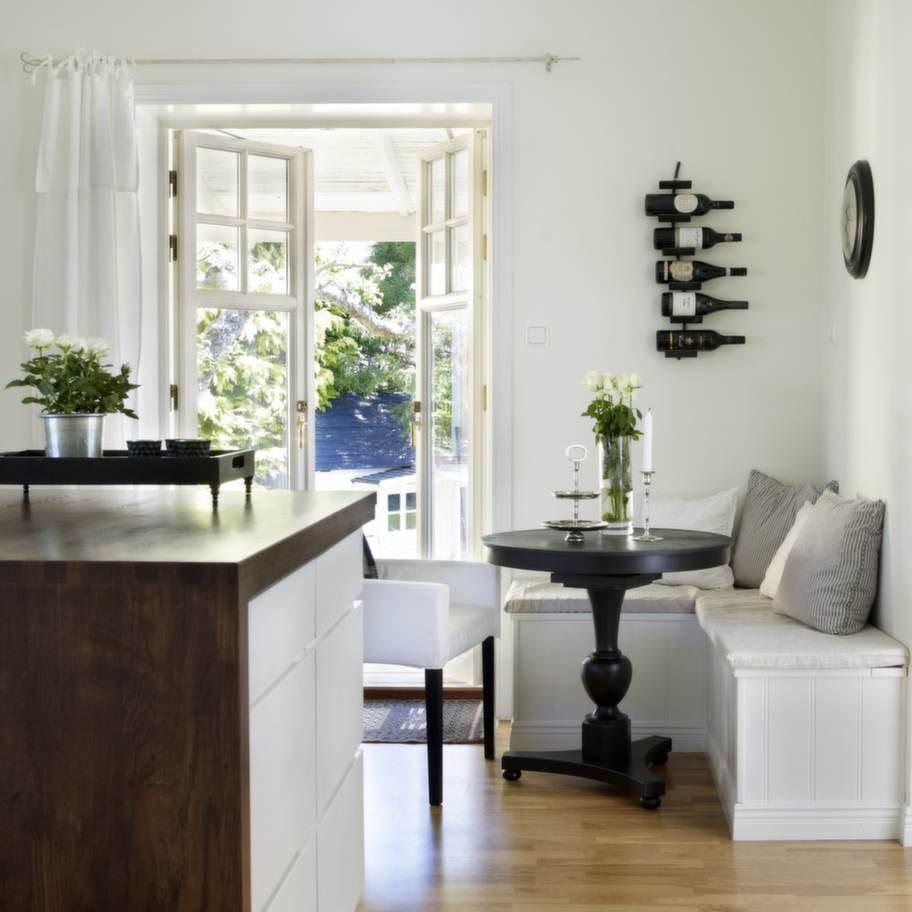 I köket ryms en liten mysig frukosthörna, där man sommartid gärna sitter och äter frukost med dörrarna på vid gavel. Bordet är ett auktionsfynd som Annette har målat svart, stolarna är från Ikea.