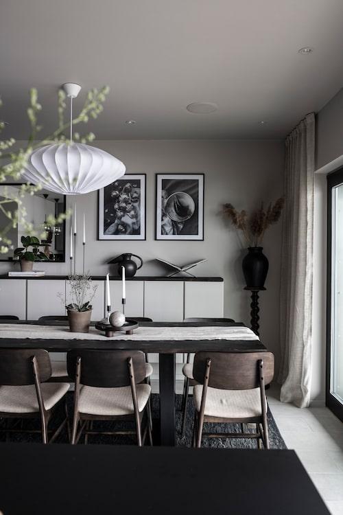 Matbordet är ett av parets alla egendesignade möbler, här i form av mörkt laserade furuskivor med svetsat underrede. Stolar, Ellos. Taklampa, Watt & Veke. Väggskåpen från Ikea och har målats i samma färgnyans som väggen. Ovanpå vilar en toppskiva i laserad furu som går ton i ton med matbordet. Piedestalen, liksom vasen ovanpå, är loppisfynd. Tavlor, Desenio.