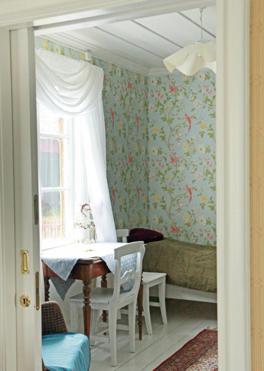Fantasifullt fågelmotivTapeten med rosa fåglar mot pastellblå botten, i ett av sovrummen, kommer från Laura Ashley.