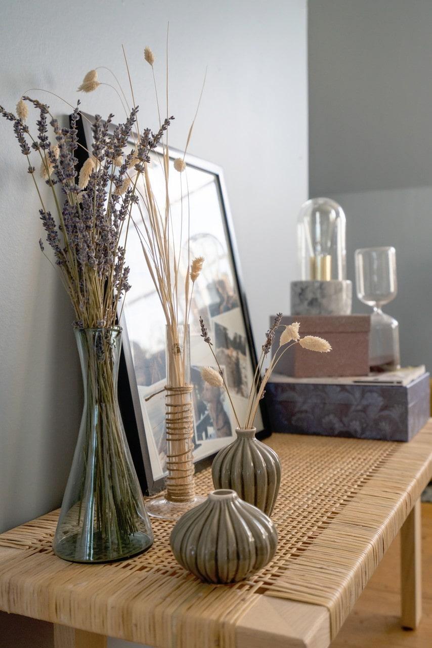 Vackert stilleben med torkade kvistar på bänken i naturmaterial.