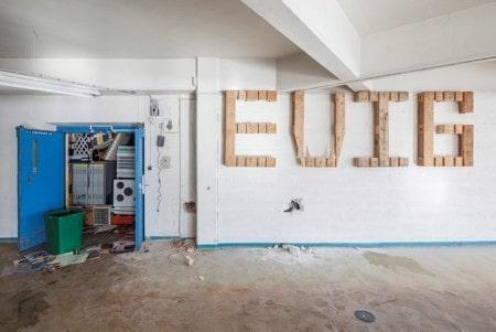 """""""Evig"""" står det i stor skrift på väggen. Texten ser ut att vara gjord av träklossar."""