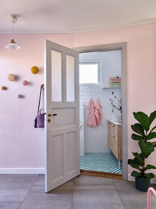 Viktors pappa har byggt den charmiga dörren som leder in i badrummet. Knoppar på hallväggen, Muuto. Väska, Acne, second hand. Klinker i badrummet från Marrakech Design.