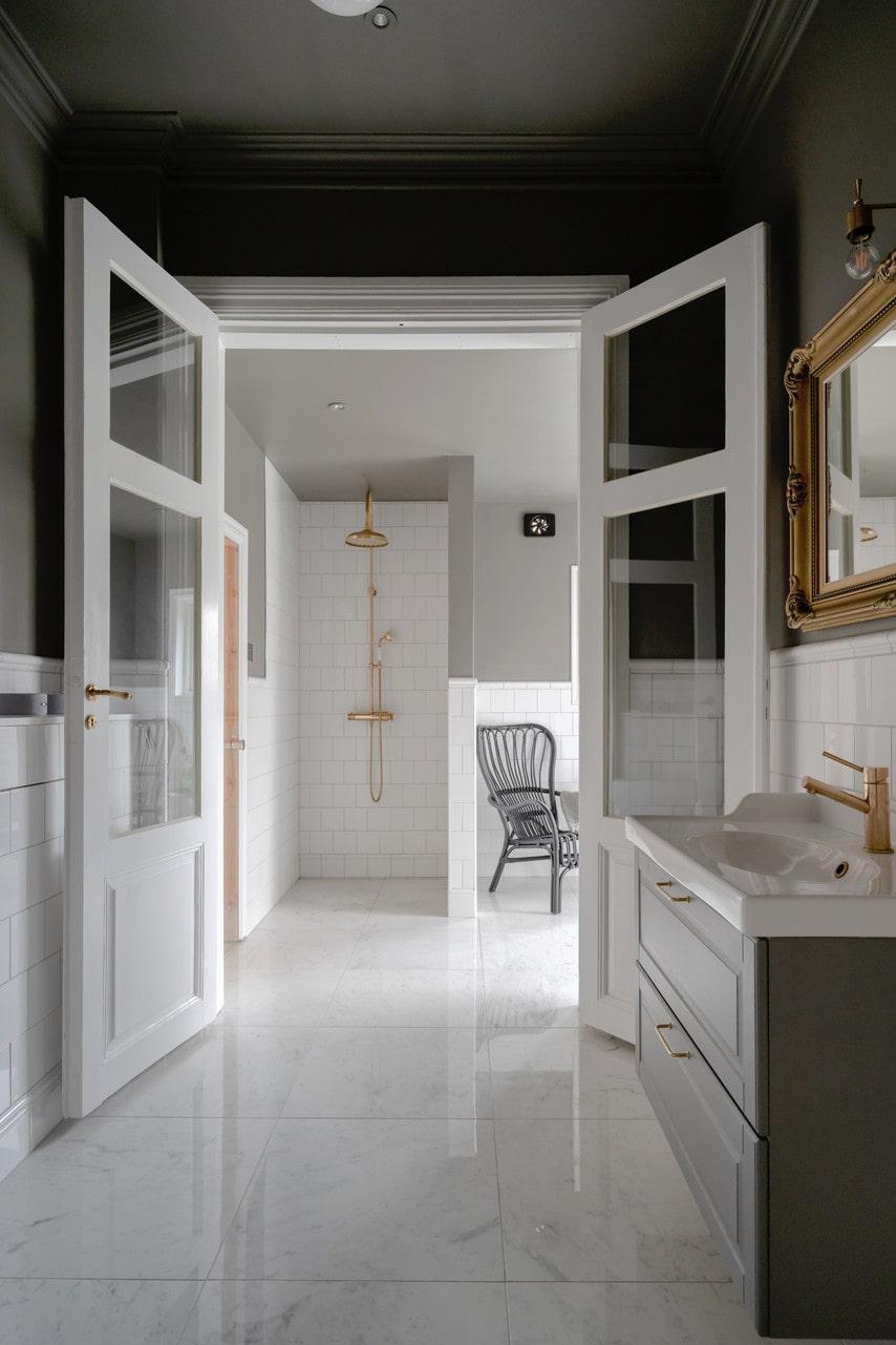 Glasade dubbeldörrar skärmar av mellan badrummet och relaxavdelningen. Takdusch, Tapwell.