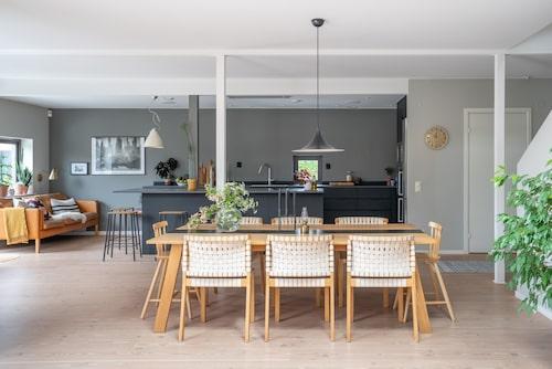 På nedre plan valde paret att måla väggarna i en gröngrå kulör förutom i köket som försågs med mörkgrå färg som kontrast. Bord och stolar, Kostallet Design. Taklampa Semi Pendel, Gubi.