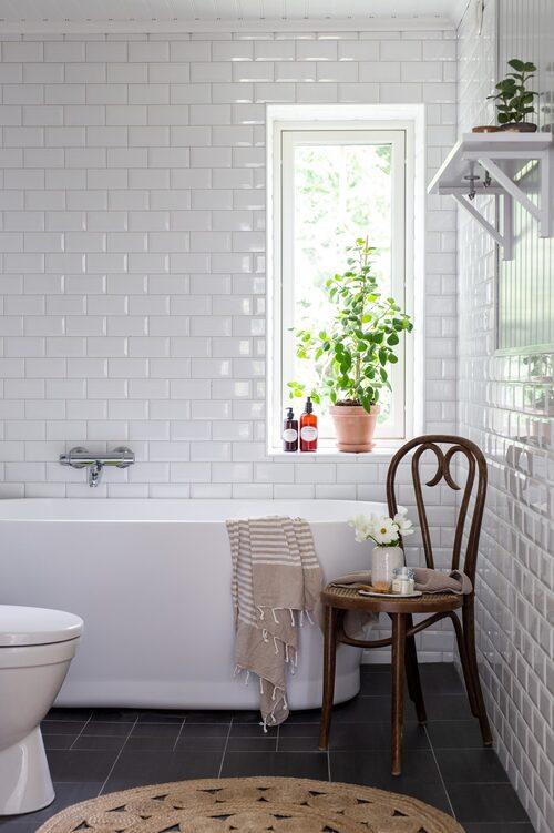 Det stilrena badrummet har, liksom köket, ett rektangulärt liggande kakel i halvförband. Badkar, Stonefactory. Matta, Jotex. Stolen är köpt på loppis. Handduk, H&M Home. Vas, Jysk. Kakel, Interkakel.