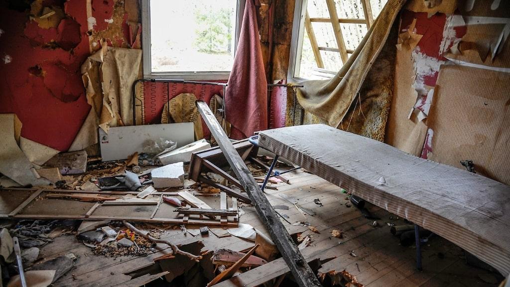 Hål i golvet, en gammal madrass på en tältsäng, utslagna fönster, gardiner som rasat ned...