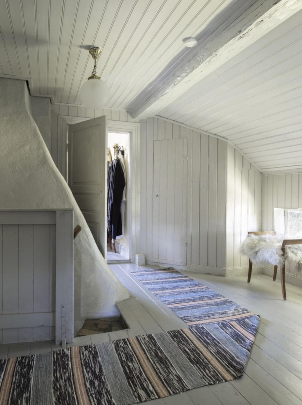 Grå toner. Hela ovanvåningen är målad med samma grå färg. Murstocken trängs bredvid den speciella trappan, där de första stegen är i tegel för att sedan övergå i trä.