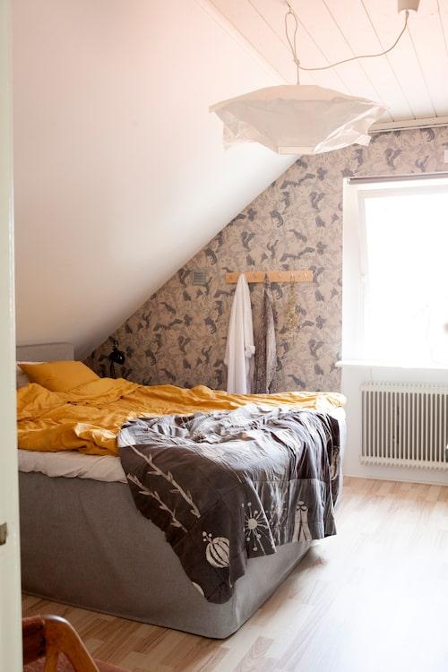Tapeten Dancing crane från Eco wallpaper pryder parets sovrum. Taklampa från Ikea, knopplist från Korgboet, och överkastet är ett lapptäcke Frida gjort i batikteknik under gymnasiet.