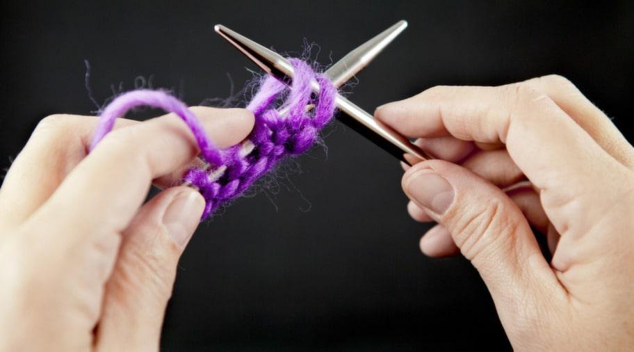 3. Lägg garnet över höger sticka. Håll ner garnet med vänster pekfinger så spänns garnet.
