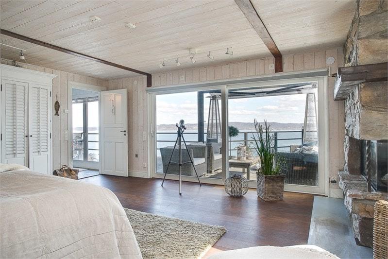 Ett stort master bedroom med öppen spis och panoramafönster med skjutdörrar mot trädäck och Vättern.
