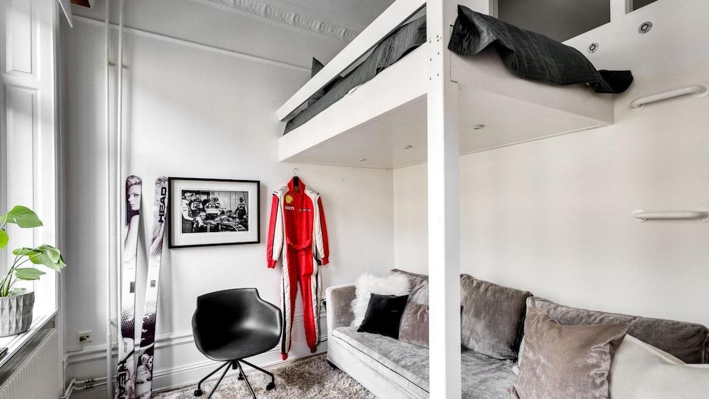 Ett mindre sovrum med två stora fönster mot Upplandsgatan. Brädgolv och vitmålade väggar. Platsbyggd loftsäng och inbyggda fönster mot hallen. Kolla in skidorna!
