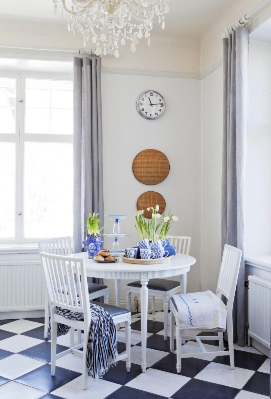 Med korgar på väggen och udda rustika tyger på stolarna gör Johanna det vackra köket extra ombonat och charmigt. Rutigt klinkergolv la de förra ägarna in.