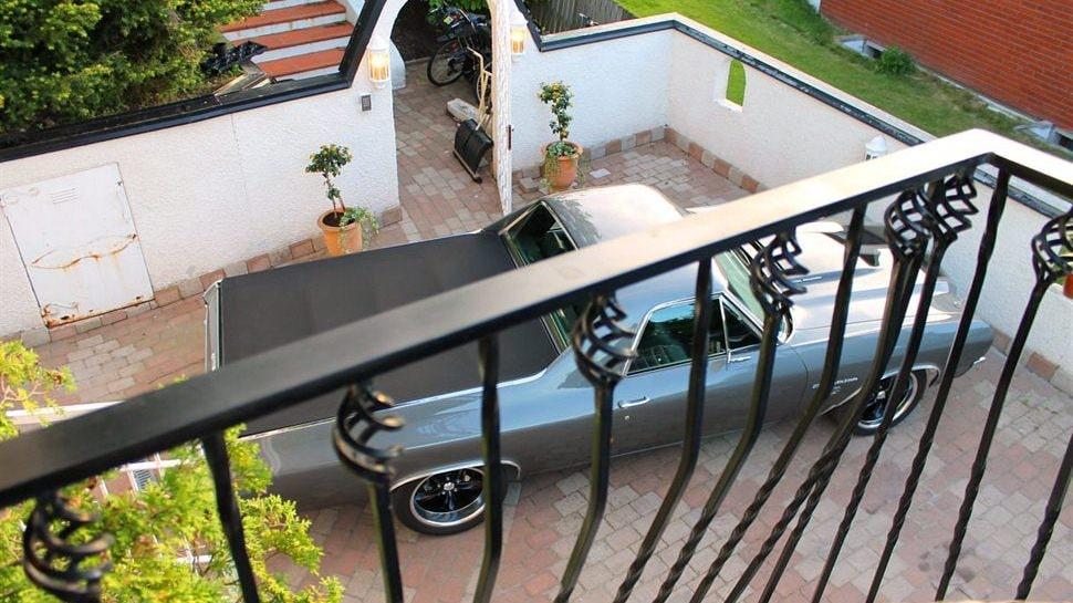 Stenlagd entré med vitmålad mur och terracottalagd spansk trappa för en direkt access till baksidans terrass. Balkong på huset med järnsmidesräcke.