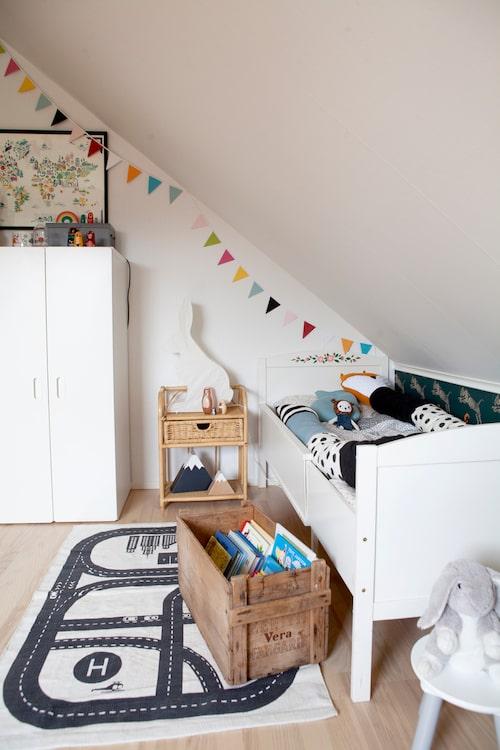Lekfullt i Cornelis rum. Sängen är Fridas gamla, nyponrosorna har hennes faster målat en gång i tiden. Även rottingbordet är Fridas gamla. Kanin från Ikea, berg och vimpel från Lagerhaus. Tapet av Lisa Bengtsson och garderob från Ikea.