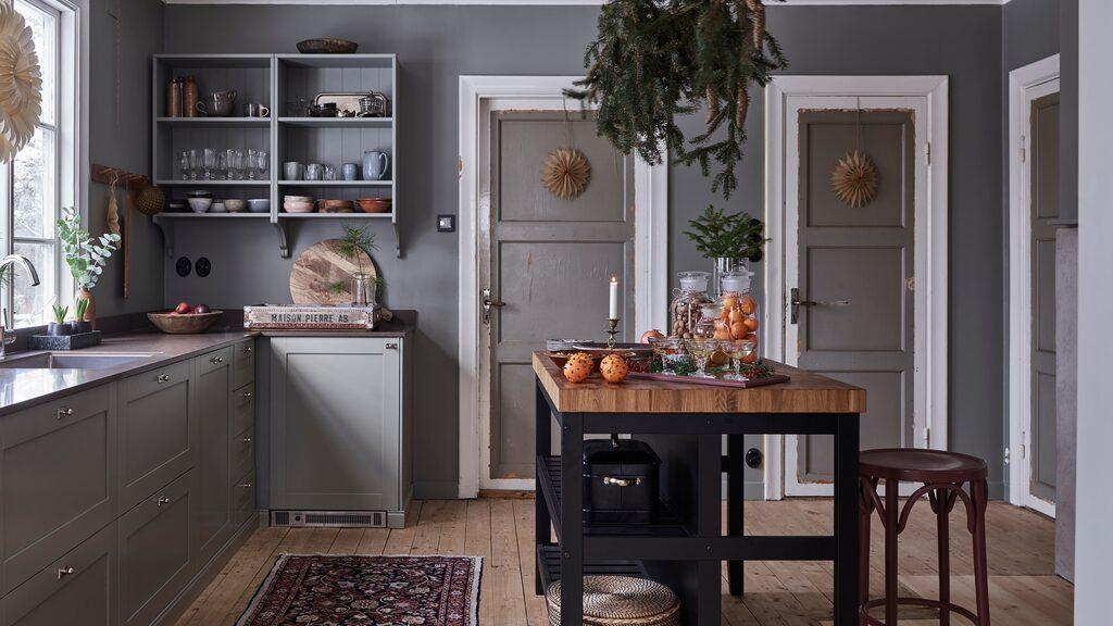 Köket från Ikea har lackerats i en grön nyans, som även återkommer på rummets väggar.
