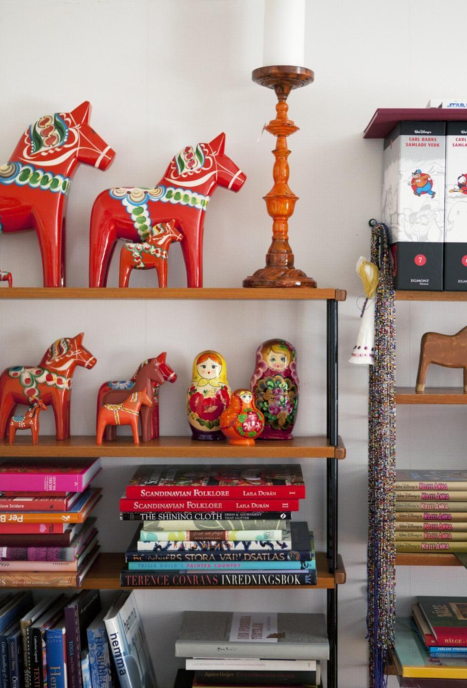 Röda hästar, böcker och saker på hyllorna gör vardagsrummet personligt.