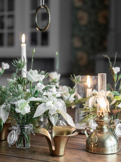 Ida har klippt av vita julstjärnor i kruka och använder dem i stället som snittblommor. De bildar ett vackert jularrangemang tillsammans med grenar av tall, granris och vackra mässingsdetaljer.