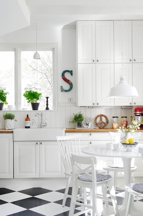 Det vita köket kommer från Ikea och ovanpå vilar en bänkskiva i massiv ek. Stänkskyddet i pärlspont, tillsammans med diskhon i porslin, ger köket en gedigen och tidsenlig känsla. Runt det vita bordet från Ikea står de klassiska stolarna Lilla Åland.