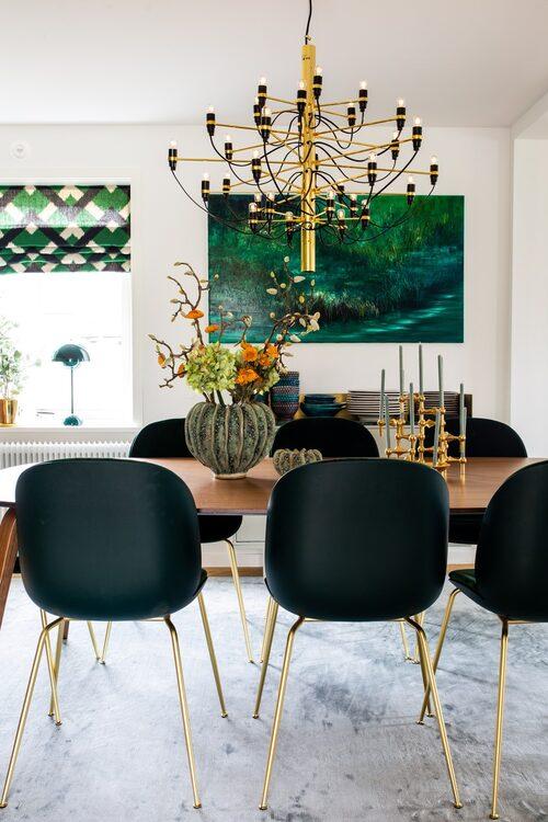 Ellipsformat matbord och grönklädda Beetle-stolar, Gubi. Taklampa Sarfatti, Flos. Oljemålning av Jolanta Nowaczyk.