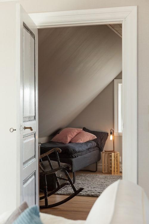 Gästrummet har ett rejält snedtak och är målat i en varmt beige ton. En pall på högkant fungerar som nattduksbord till övernattande gäster.