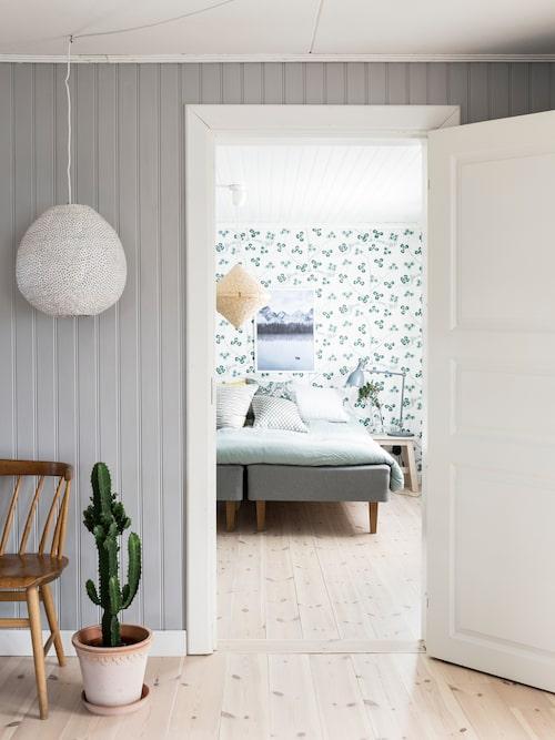 Väggen med pärlspont är målad i en behaglig grå ton som passar fint ihop med inredningen i rummet.