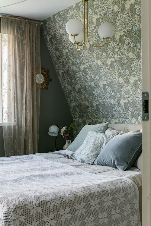 Sovrummet med snedtak har tapetserats med tapeten Seaweed från William Morris. Sänggaveln består av en gammal dörr. Det virkade överkastet ligger ovanpå en av Lindas stora linnedukar. Kuddar, från H&M Home och Home & Cottage. Taklampa, Mio.