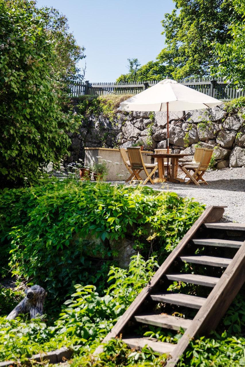 Uteplatsen är möblerad med trädgårdsmöbler köpta på Blocket. I bakgrunden syns grillplatsen. Parasoll, Bauhaus.