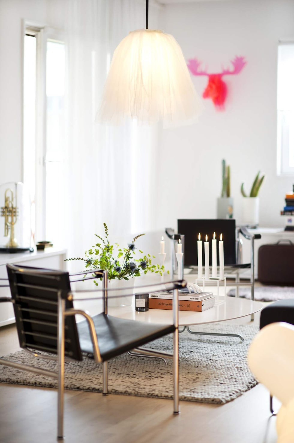 I allrummet står fåtöljerna Le corbusier LC1 tillsammans med soffbord och bänkar från Asplund. Taklampan som påminner om en ballerinakjol är designad av Jonas Bohlin. På väggen hänger en rosa Moose trophy från Catrines företag Cooee design.